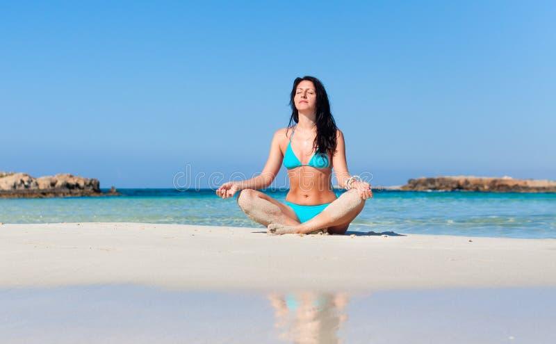 Femme méditant sur la plage image stock
