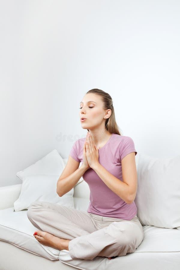 Femme méditant sur le sofa images stock