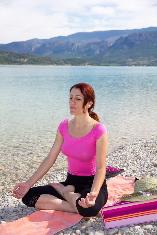 Femme méditant sur un au bord du lac. photo libre de droits