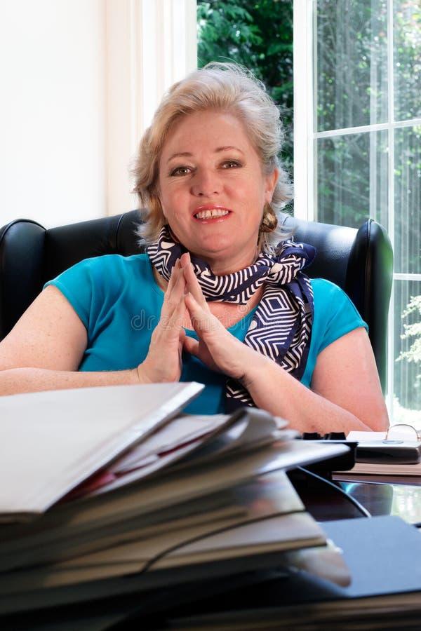 Femme mûr à son bureau, souriant photo libre de droits