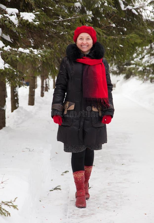 Femme mûr au stationnement de l'hiver photos stock