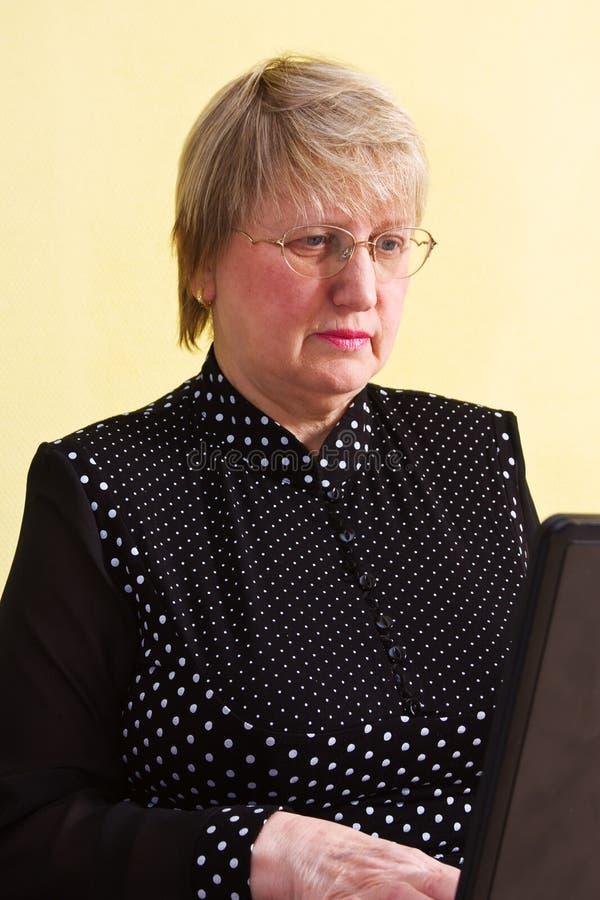 Femme mûr avec l'ordinateur portatif photographie stock
