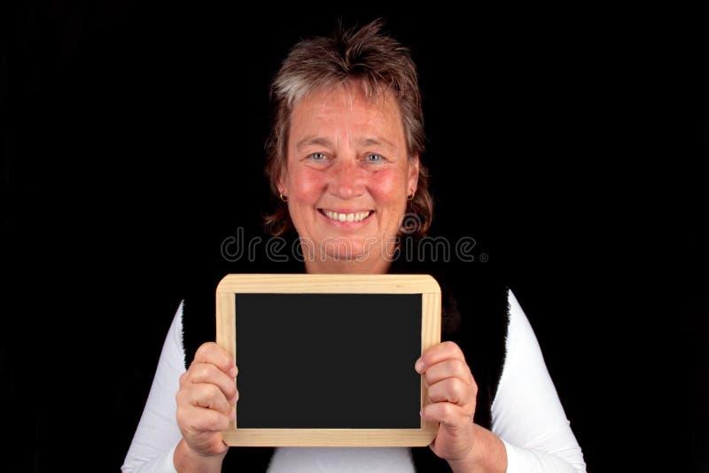 Femme mûr avec un panneau noir photo stock