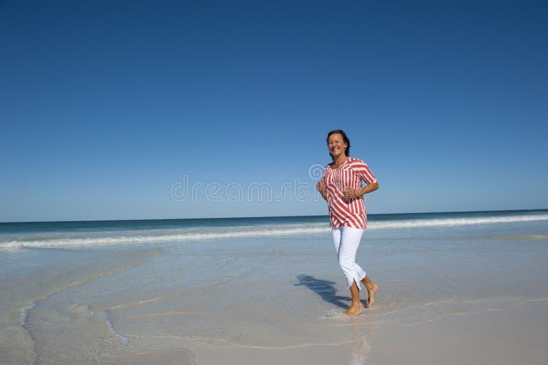 Femme mûr courant à la plage photographie stock