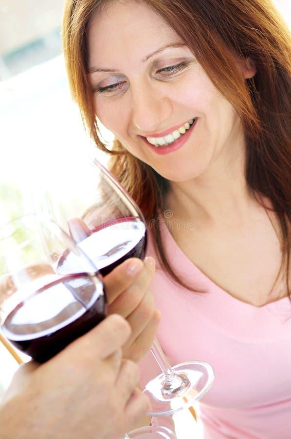 Femme mûr grillant avec le vin rouge images stock