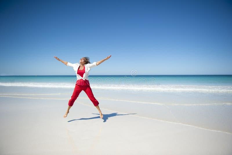 Femme mûr heureux à la plage tropicale photographie stock