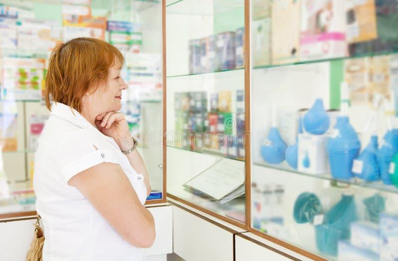 Femme mûr r dans la pharmacie images libres de droits