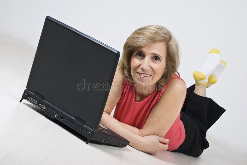 Femme mûr se trouvant sur l'étage en bois utilisant l'ordinateur portatif image stock