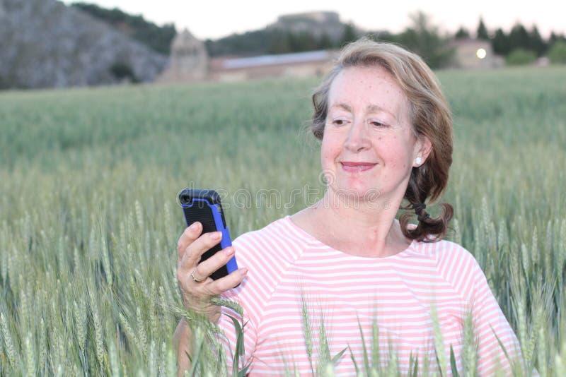 Femme mûre à l'aide du téléphone portable en nature images libres de droits