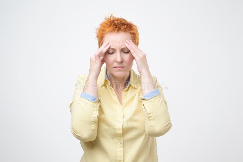 Femme mûre épuisée touchant sa tête avec des yeux fermés Souffrance du mal de tête insupportable images stock