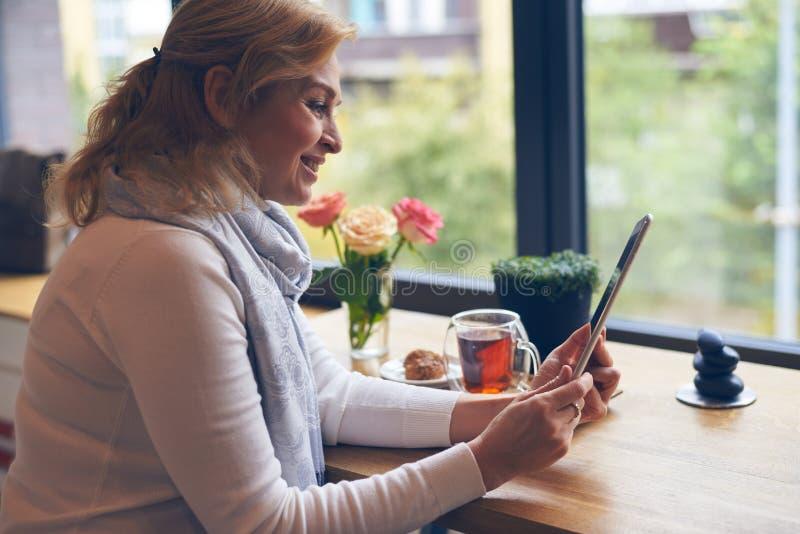 Femme mûre affectueuse à l'aide du comprimé pendant le petit déjeuner en café images stock