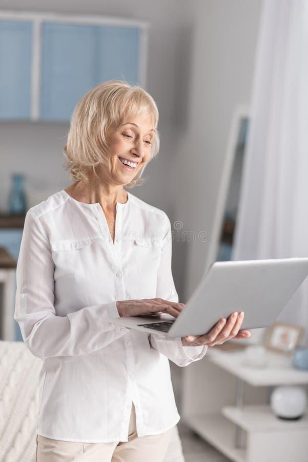 Femme mûre avec du charme causant en ligne photos stock