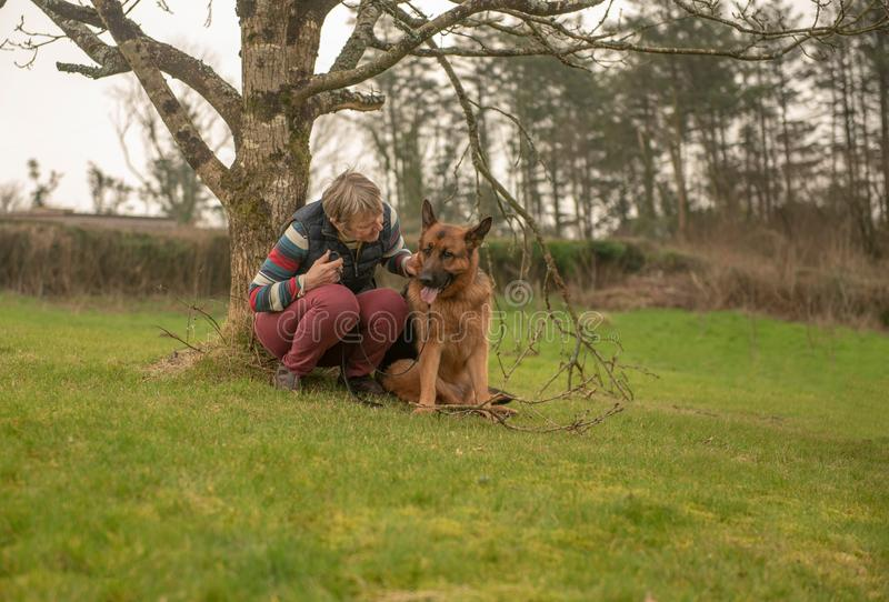 Femme mûre avec l'Alsacien d'animal familier photographie stock libre de droits