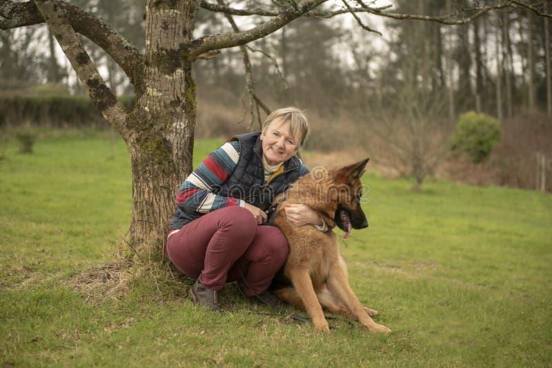 Femme mûre avec l'Alsacien d'animal familier photos stock