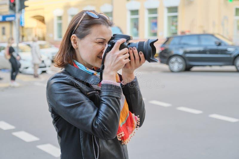 Femme mûre avec la caméra de photo photographiant sur la rue de la ville de ressort, photographe professionnel féminin, l'espace  images stock