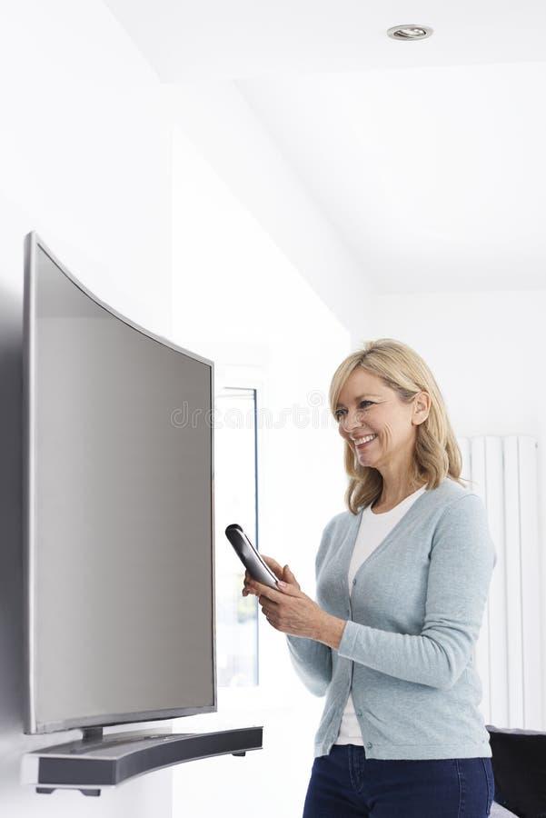 Femme mûre avec la nouvelle télévision incurvée d'écran à la maison photos libres de droits