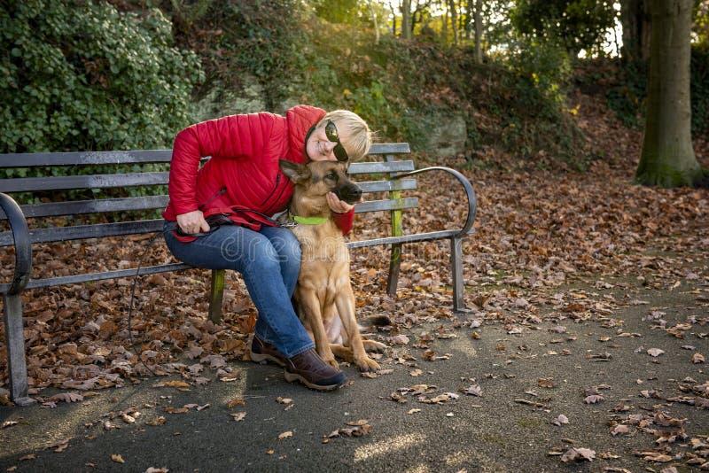 Femme mûre avec le chien alsacien en parc photos libres de droits