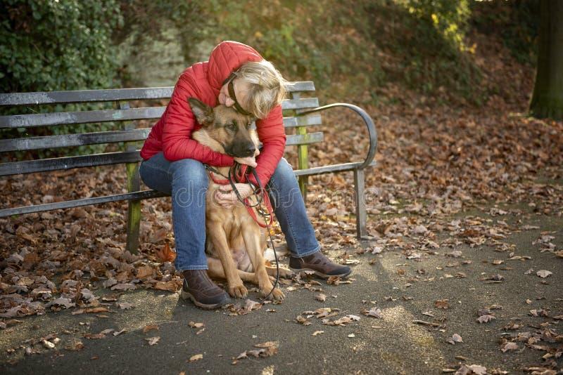Femme mûre avec le chien alsacien en parc images stock