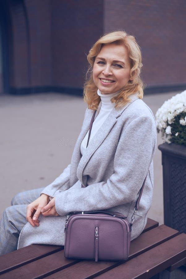 Femme mûre blonde de sourire posant à l'appareil-photo photo stock