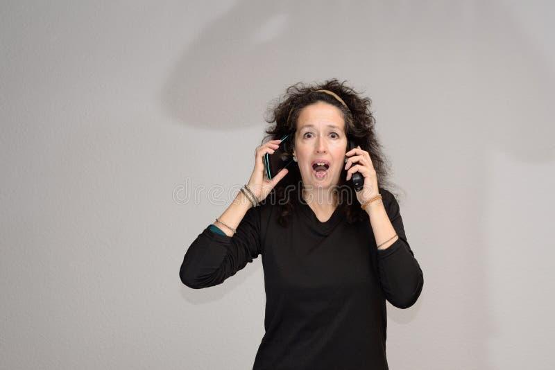 Femme mûre choquée avec la bouche ouverte de deux téléphones portables images libres de droits