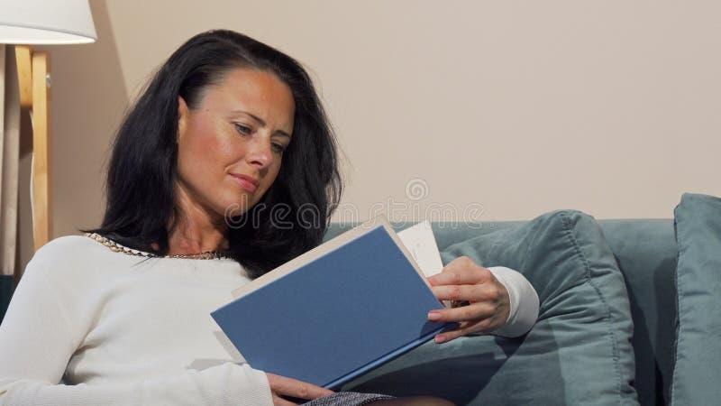 Femme mûre décontractée appréciant lisant un livre sur le divan à la maison image libre de droits