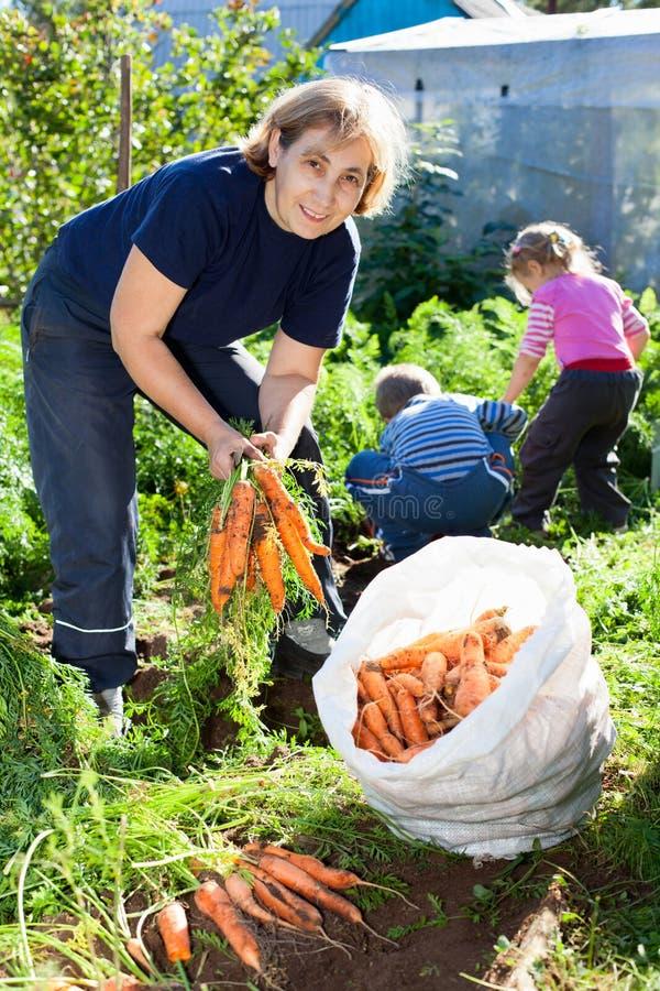 Femme mûre dans le jardin avec des enfants image stock