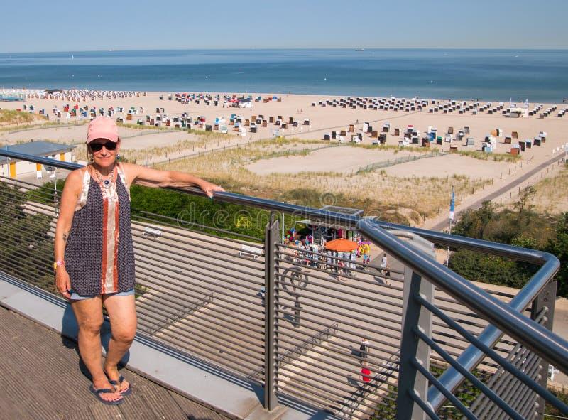 Femme mûre de baby boomer posant sur la plage de négligence de balcon et photographie stock