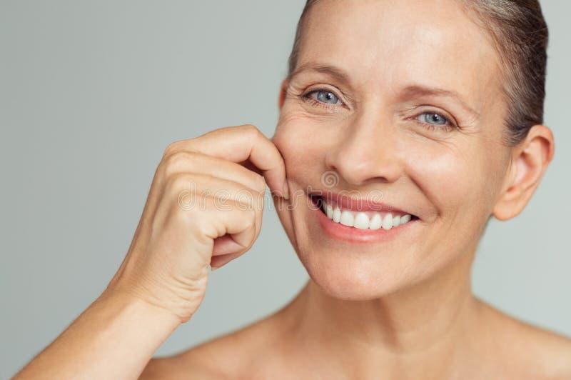 Femme mûre de beauté tirant la peau parfaite photos libres de droits