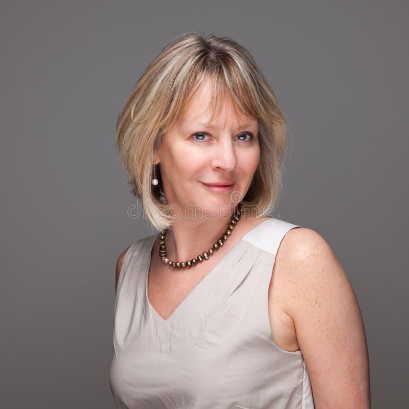 Femme mûre de sourire attirante sur le gris image stock