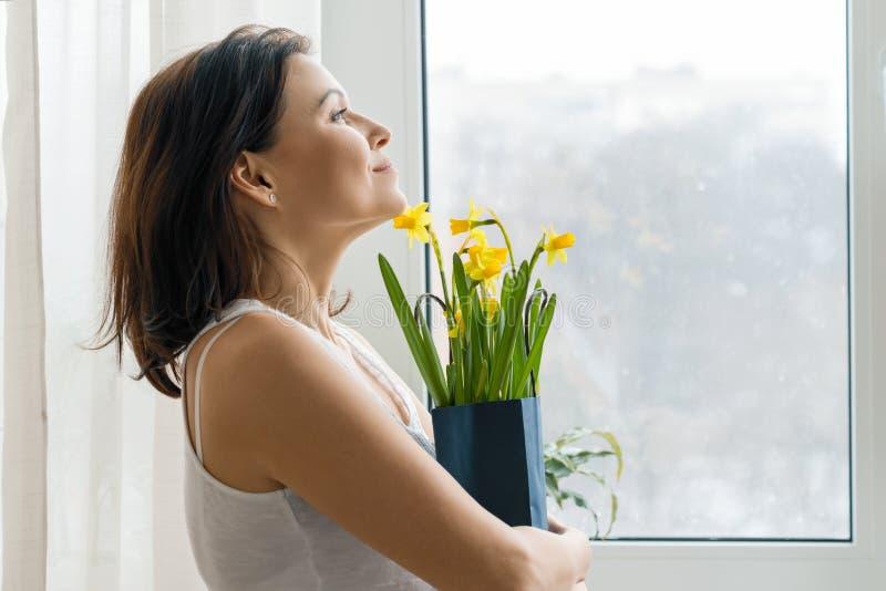 Femme mûre de sourire heureuse avec le bouquet des fleurs jaunes se tenant à la maison près de la fenêtre, printemps images stock