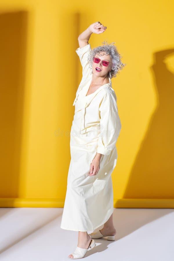 Femme mûre et élégante dans des lunettes brillantes montrant sa féminité images libres de droits