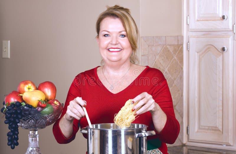 Femme mûre faisant cuire des pâtes. image stock