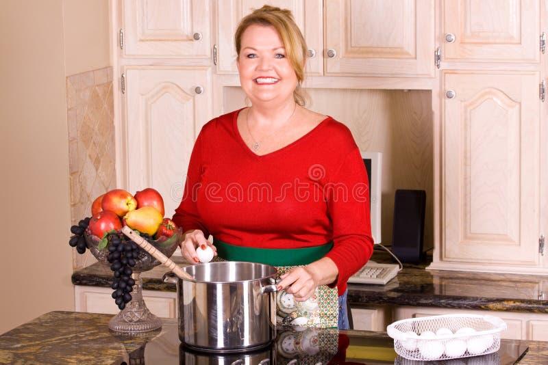 Femme mûre faisant cuire des pâtes. photographie stock
