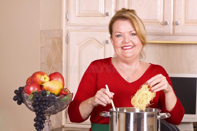 Femme mûre faisant cuire des pâtes. photographie stock libre de droits