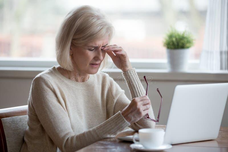 Femme mûre fatiguée enlevant des verres souffrant du stra d'oeil images libres de droits