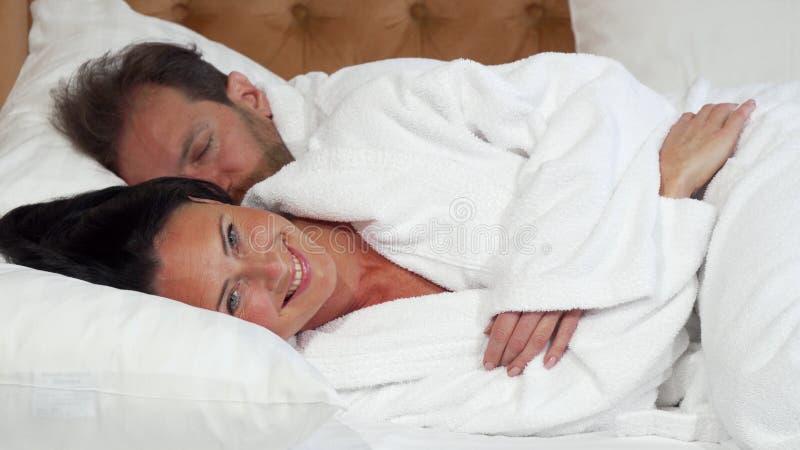 Femme mûre gaie allant dormir se situant dans le lit avec son mari photos stock