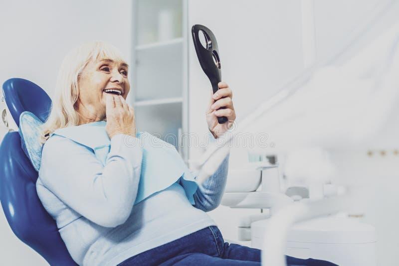 Femme mûre gaie s'asseyant dans le coffret de dentiste photos stock