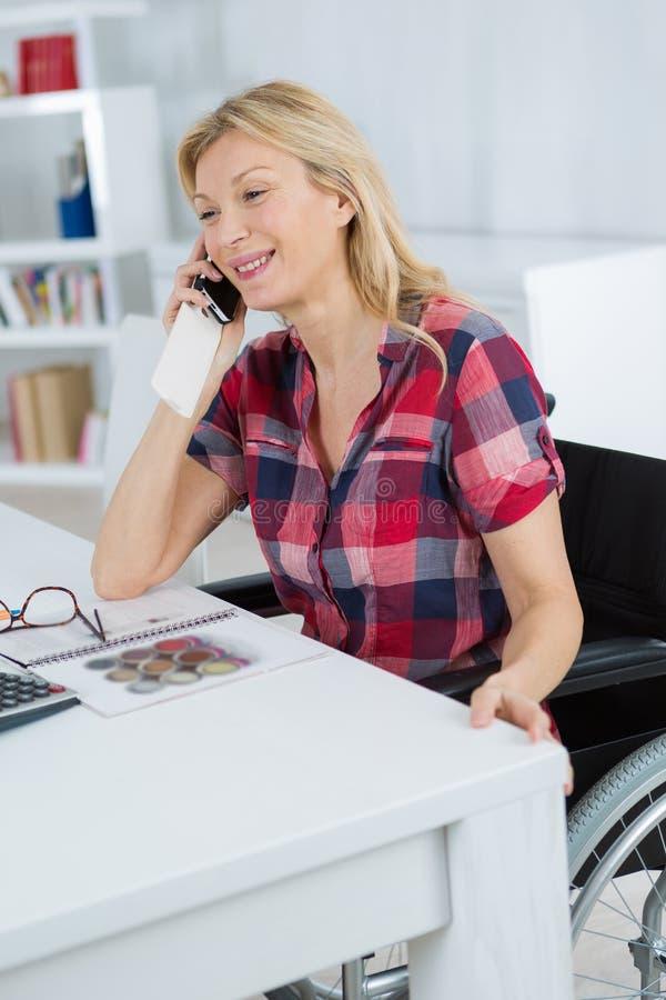 Femme mûre handicapée au téléphone à la maison photo libre de droits