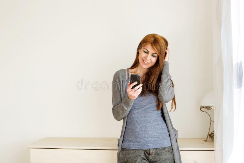 Femme mûre heureuse à l'aide du téléphone portable à la maison images libres de droits