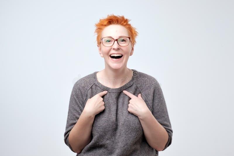 Femme mûre heureuse avec les cheveux rouges dirigeant des doigts à elle-même Svp sélectionnez-moi concept photo libre de droits