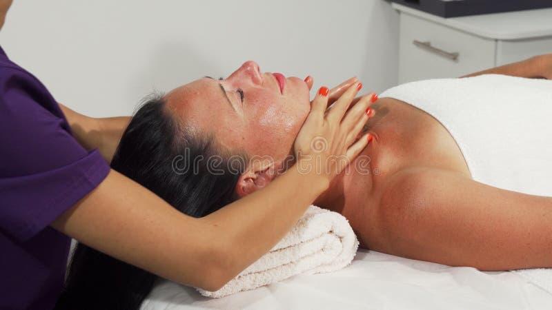 Femme mûre heureuse recevant le massage de chef et de cou photos stock