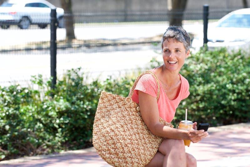 Femme mûre heureuse s'asseyant dehors avec la boisson et à l'aide du téléphone photographie stock