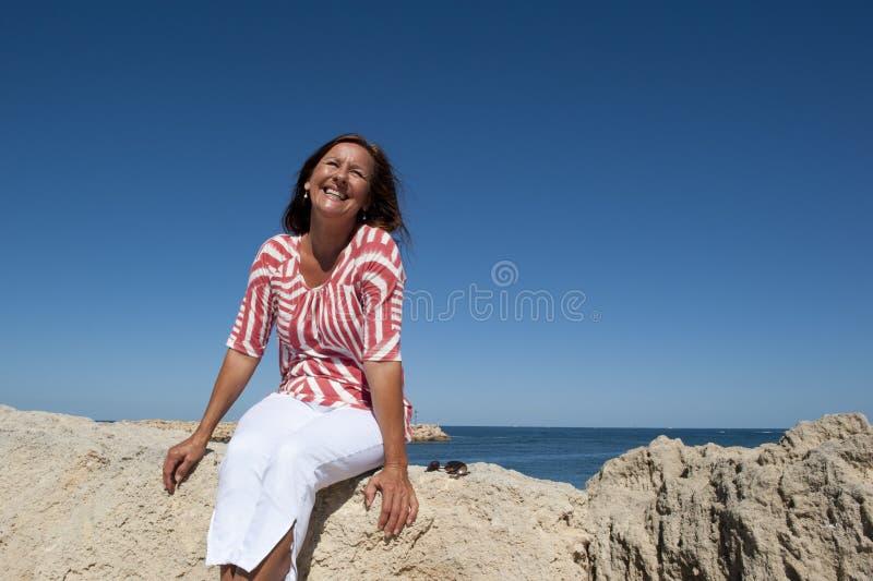 Femme mûre heureuse s'asseyant sur des roches images stock