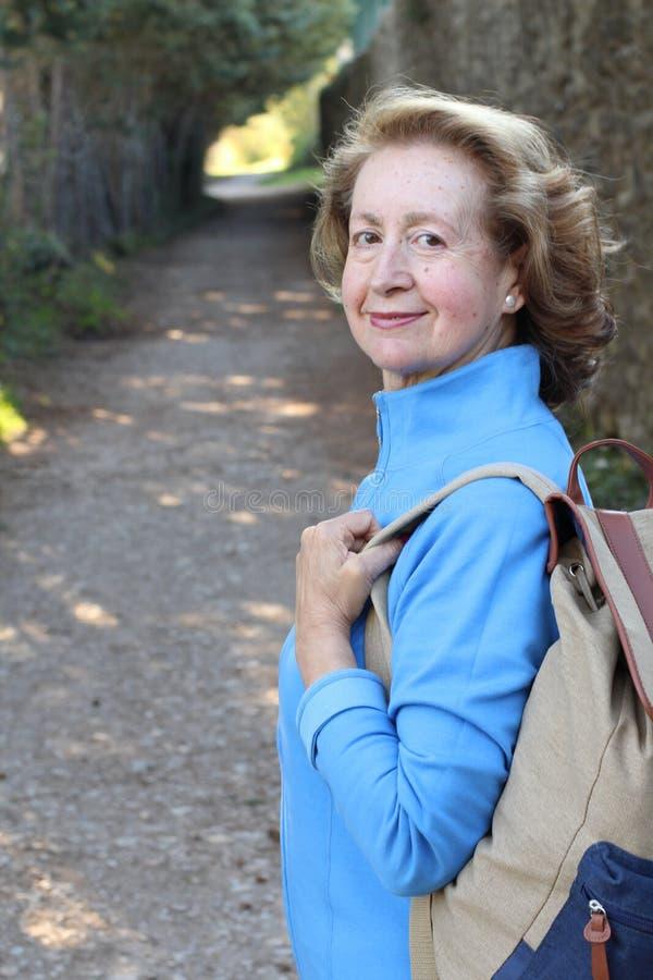 Femme mûre mignonne souriant en parc avec l'espace de copie photo libre de droits