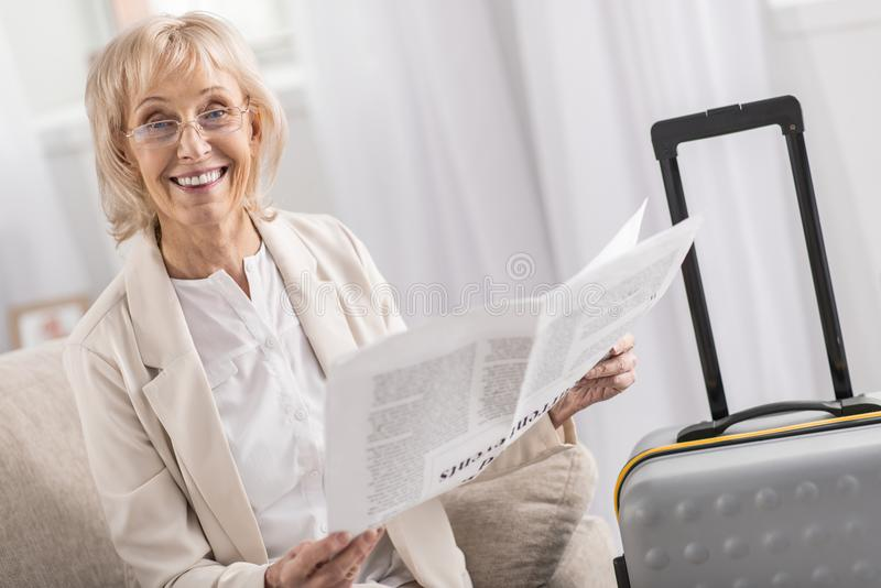 Femme mûre positive lisant près de la valise photographie stock