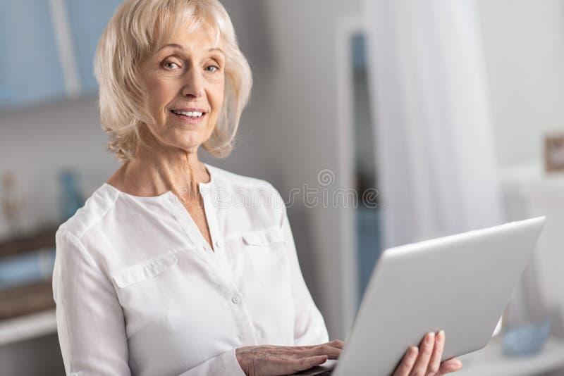 Femme mûre réfléchissante étudiant en ligne photo stock