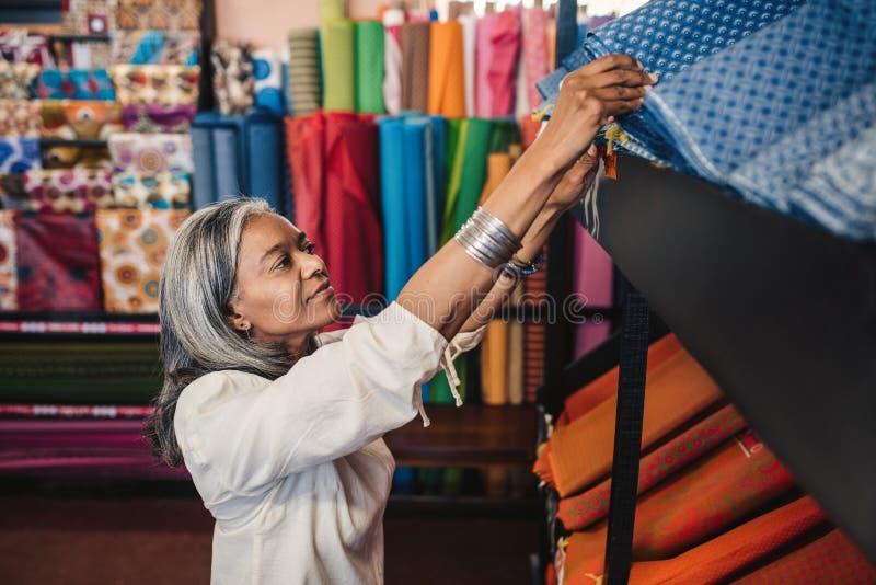 Femme mûre regardant par des petits pains de tissu dans une boutique de tissu images stock