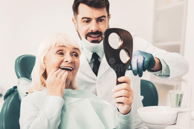 Femme mûre regardant ses dents photo stock