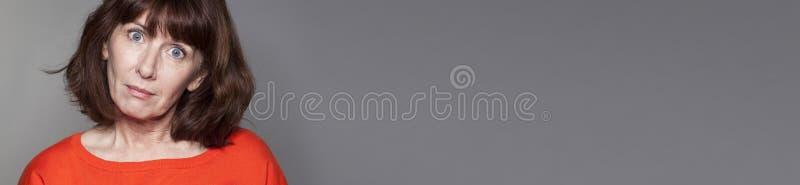 Femme mûre regardante fixement regardant sous le choc pour la saison d'hiver images stock