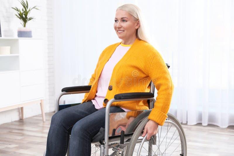Femme mûre s'asseyant dans le fauteuil roulant image libre de droits